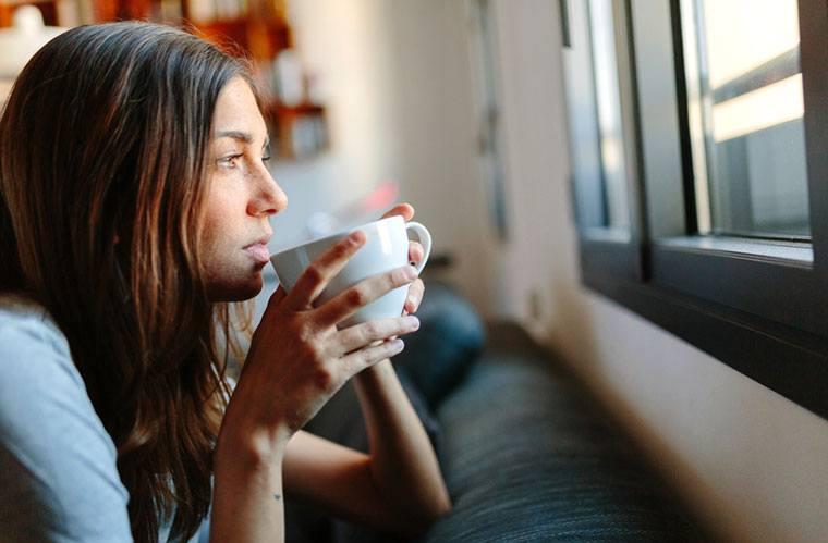 vrouw thuis een kopje koffie drinken