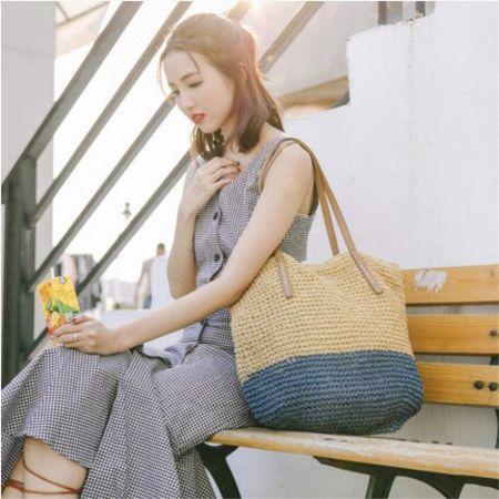 vrouw zat op bankje met strandtas