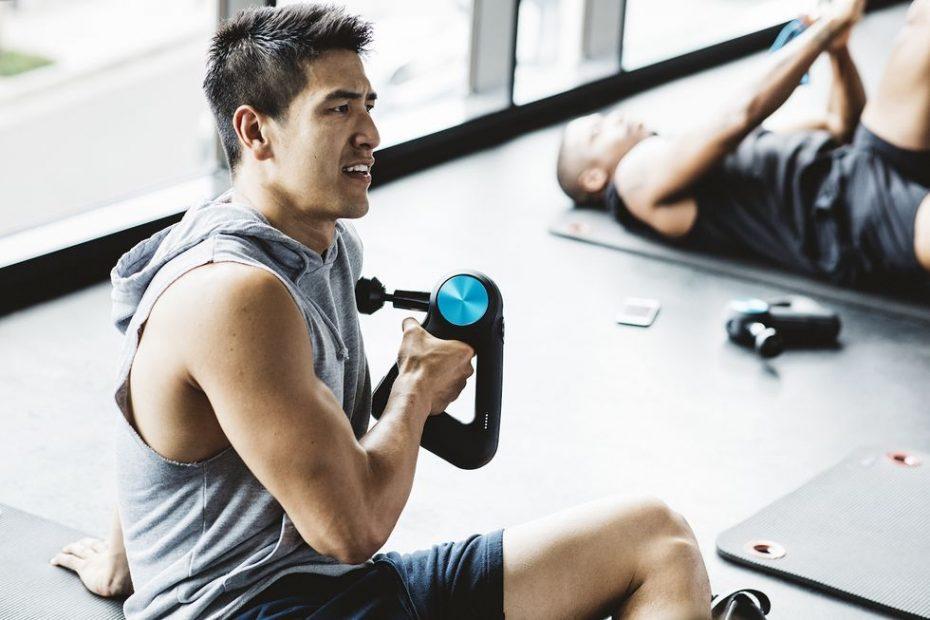 man met behulp van een massage-apparaat in de sportschool