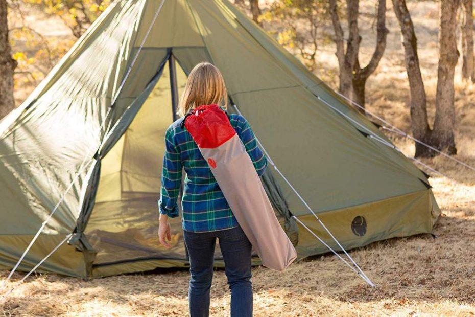 een vrouw die buiten kampeert met een tipi-tent
