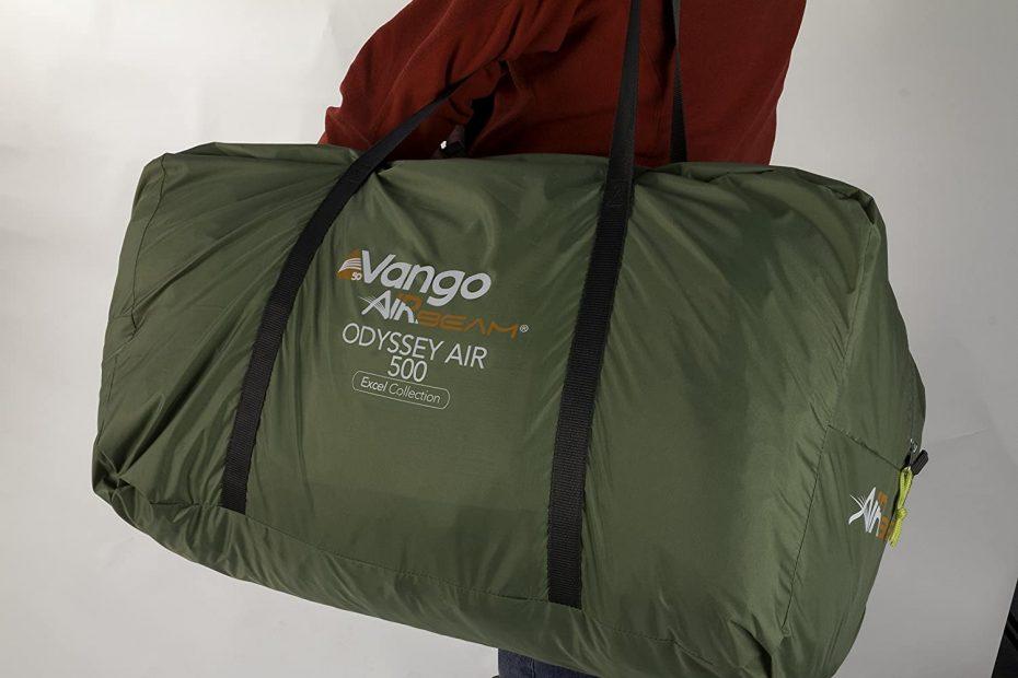 een man met een Vango opblaasbare tent in een draagtas