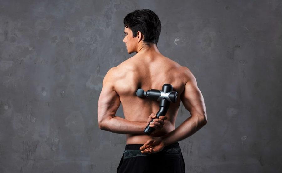 een man die een rugmassage-apparaat op zijn rug gebruikt
