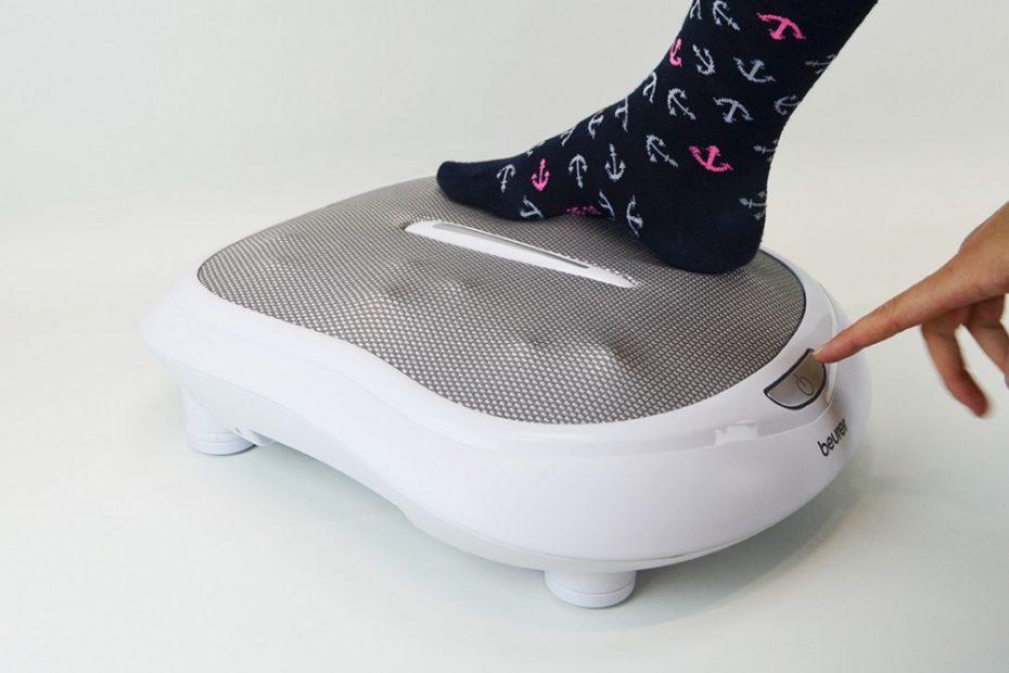 een vrouw die haar voet op een Beurer-voetmassage-apparaat plaatst
