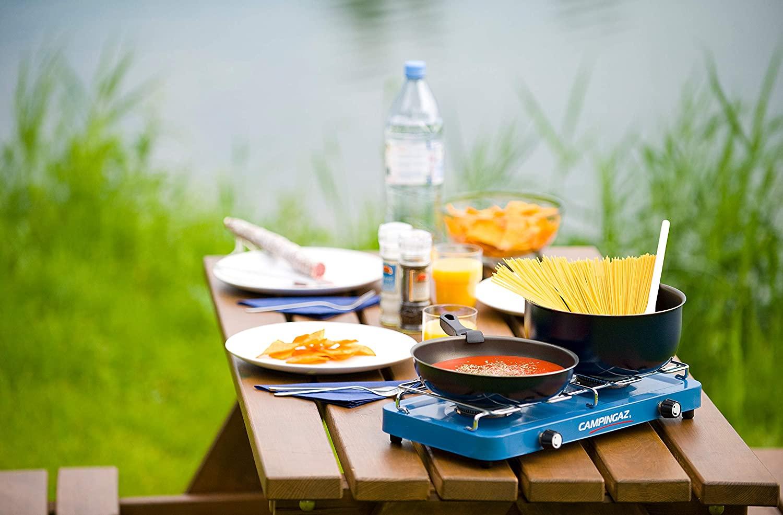 een campinggasfornuis op een campingtafel omgeven door eten