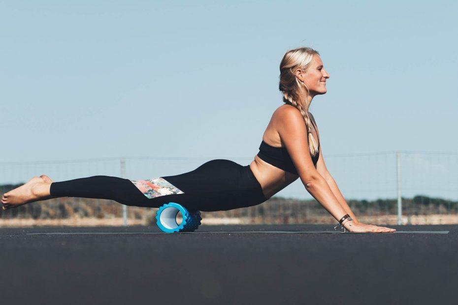 een vrouw die een schuimroller gebruikt om oefeningen te doen