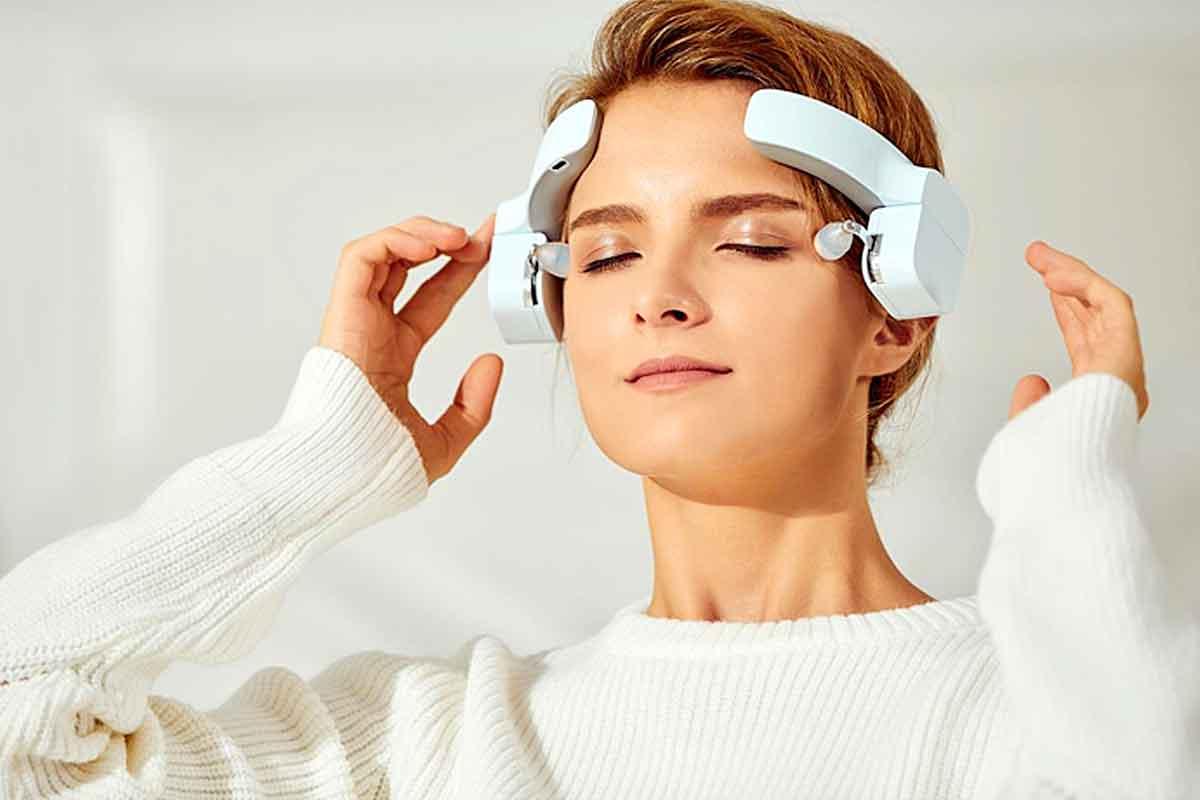 een vrouw die een hoofdmassage-apparaat gebruikt om te ontspannen
