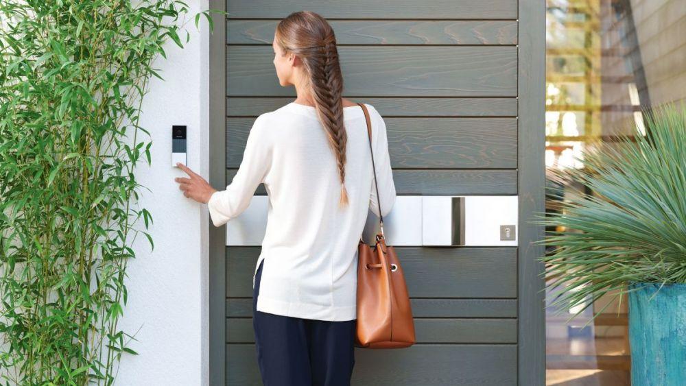 een vrouw die een deurbel met camera gebruikt bij de voordeur van haar huis