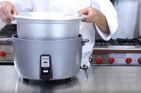 een chef-kok die een rijstkokerpan in de rijstkoker plaatst