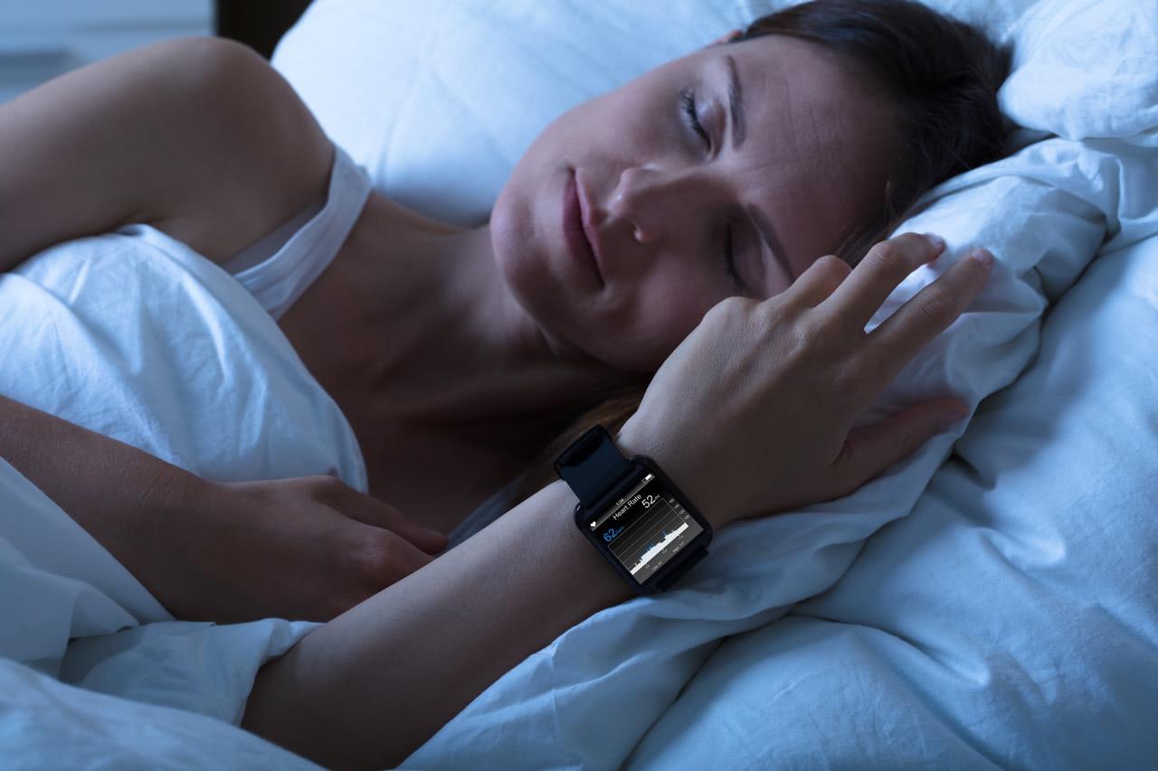 een vrouw die op een bed slaapt met een slaaptracker horloge