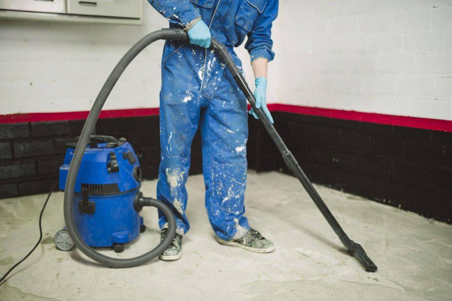 een man in overall met behulp van een bouwstofzuiger op een bouwplaats