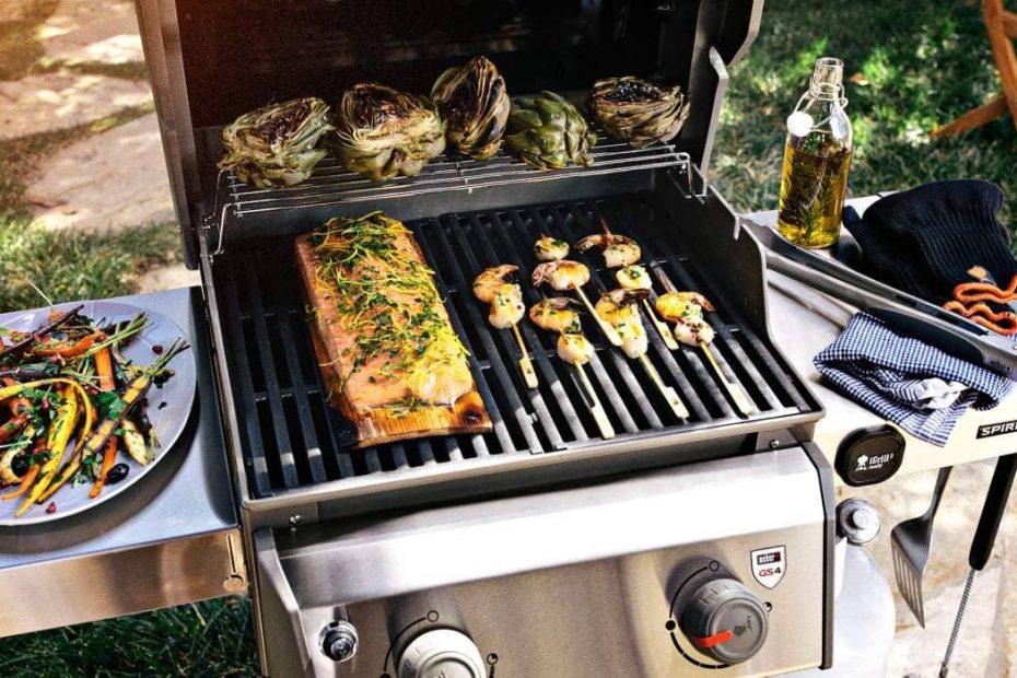 een gasbarbecue met daarop gegrilde kip