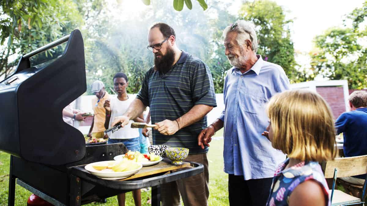 een gezin stond rond een gas barbecue te barbecueën