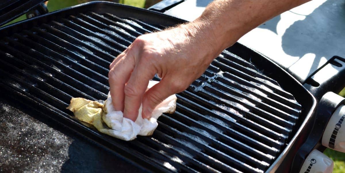 een man die de grill van zijn gasbarbecue schoonmaakt