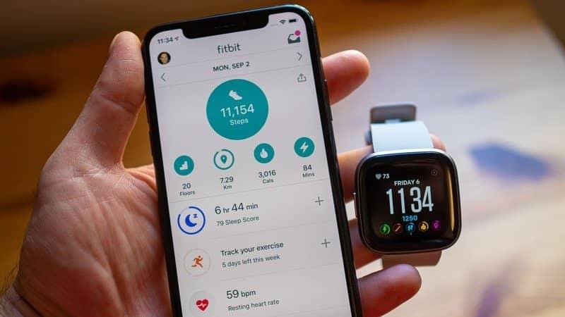 een man met een smartphone en Fitbit Versa in zijn hand