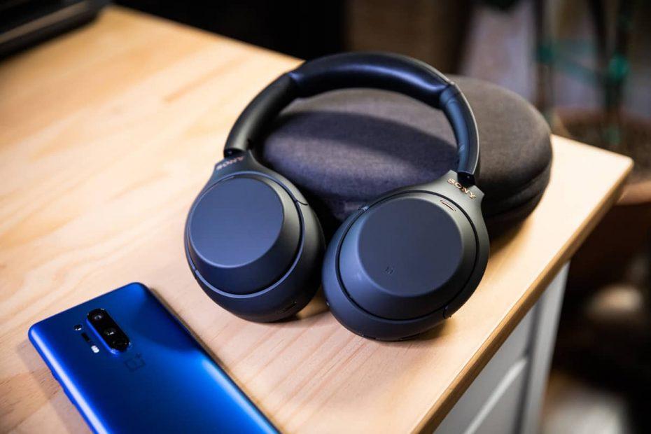een nieuwe zwarte koptelefoon naast een smartphone op een tafel